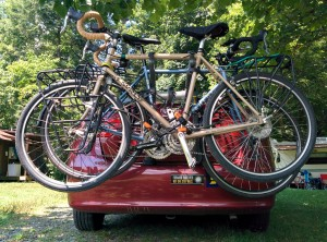 Surly and Bianchi touring bikes on a trunk rack of a borrowed car which is parked in the shade of a tree in a corner of Camp Celo